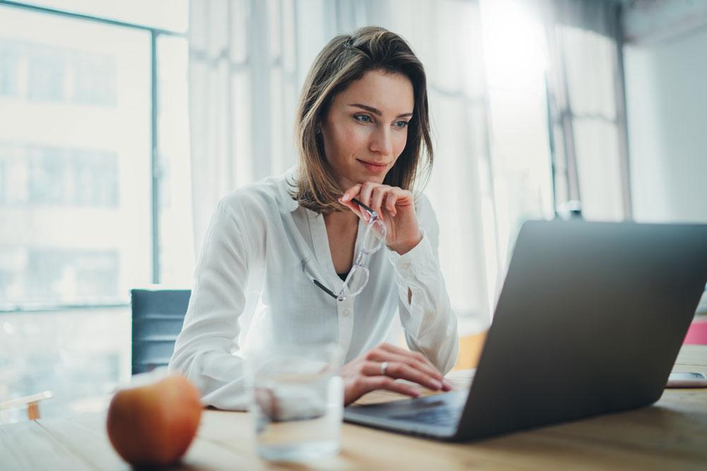 Uma mulher está sentada em uma mesa em seu computador.