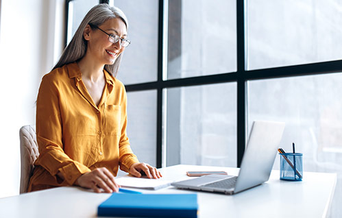A person smiles while sitting at a desk and looking at their laptop.