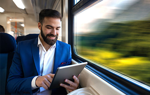 Um homem de terno está sentado em um trem em movimento enquanto sorri segurando um tablet.