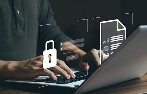 Foto de close de um laptop com um homem sentado digitando nele e ícones gráficos flutuando acima
