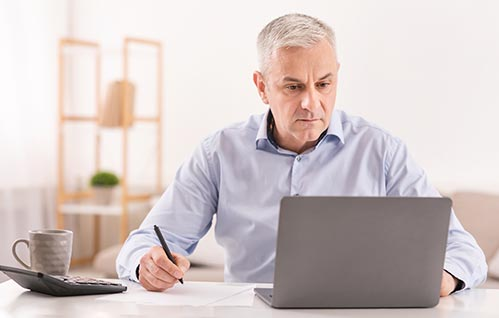 An older man sits at a desk looking at a laptop screen