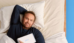 A man lying in his bed with a box
