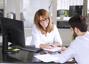 Man and woman at a desk with a computer - Real Profit Business Solutions - Bookkeeping