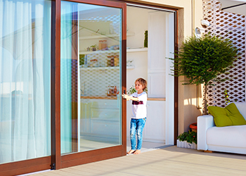 Home exterior with a sliding door and small child - Sliding Door Repairs