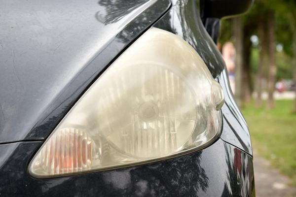 close up of dull headlight on dark sedan