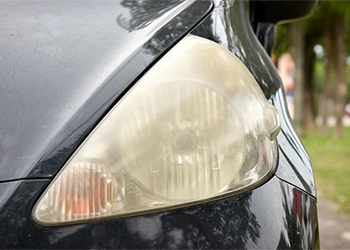 close up of dull headlight on dark sedan