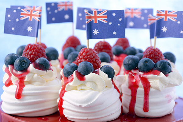 mini pavlovas with berries in front of Australian flags