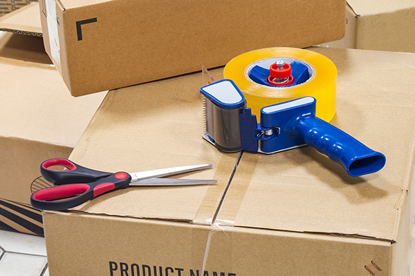 Packing boxes with scissors and packing tape