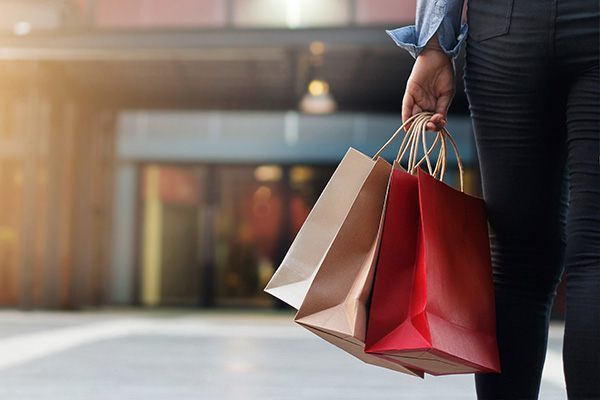 Woman walking in shopping mall holding multiple shopping bags