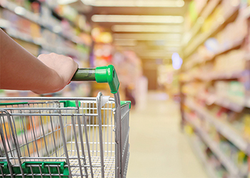 Person pushing shopping trolley in supermarket