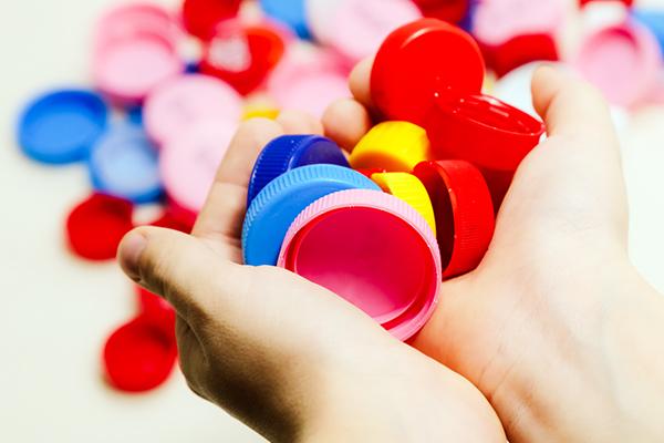 Hands holding assorted plastic bottle caps