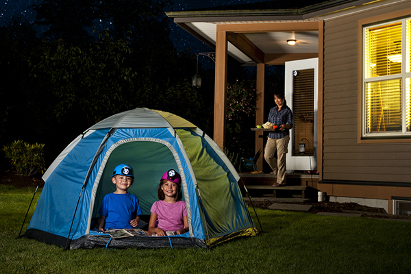 2 kids in a tent pitched in backyard