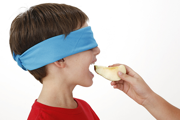Young boy with blindfold eating healthy food