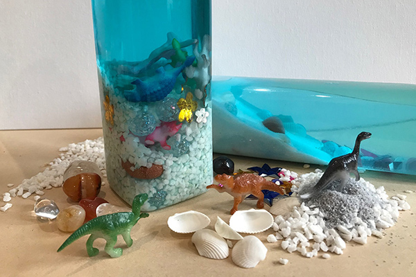 make your own sensory bottle with dinosaurs and shells