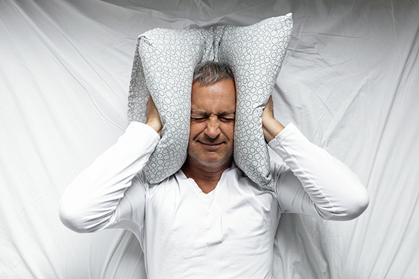 man covering his ears with pillow