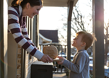 Child giving homemade bread to his neighbour