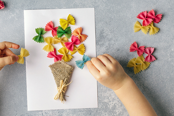 Small child making a picture with coloured pasta