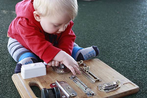 Toddler playing with a busy board