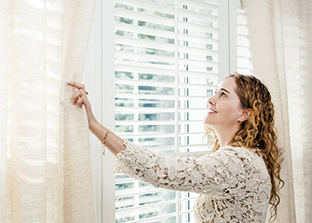 Woman opening curtains to reveal a window with blinds