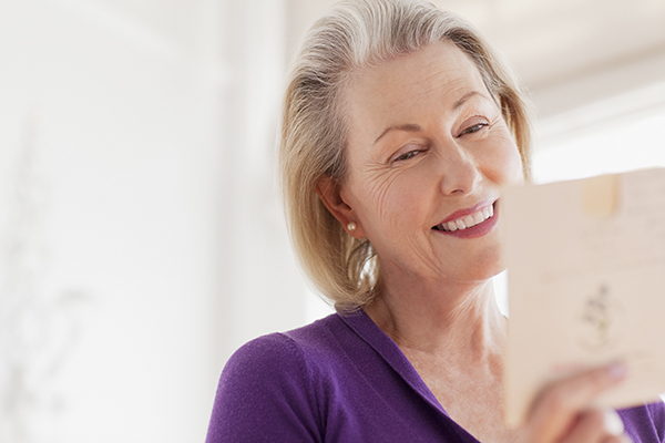 Happy older lady reading the inside of a card