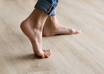 Person walking barefoot on floorboards