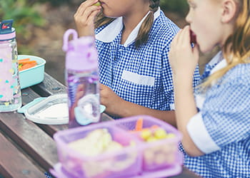 Two schoolgirls eating lunch from lunchboxes