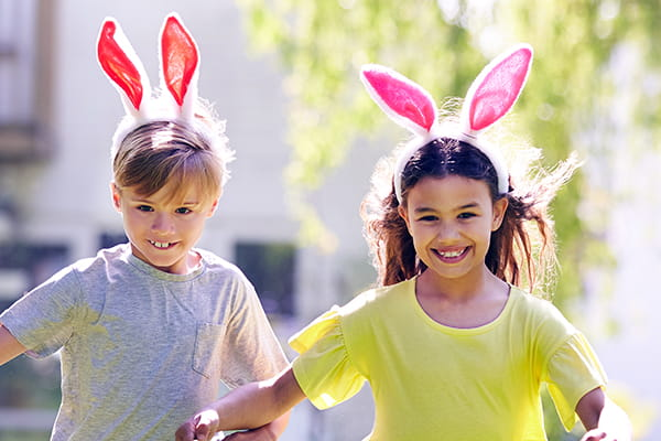 Two children outdoors wearing bunny ears