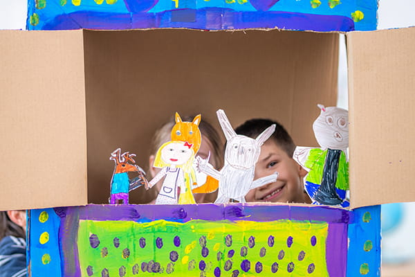Kids playing with a homemade cardboard box puppet theatre