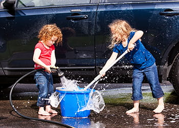 Two children washing a car