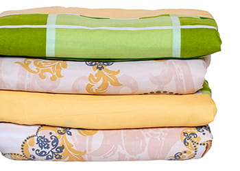 Various bed sheets in a folded pile
