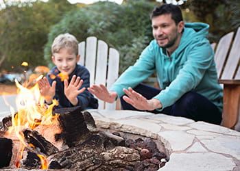 family sitting around firepit