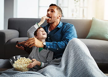 father and son eating popcorn