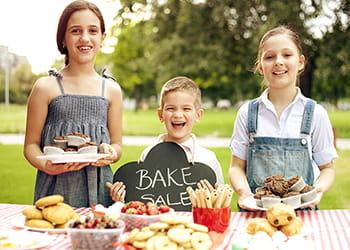three children having a bake sale
