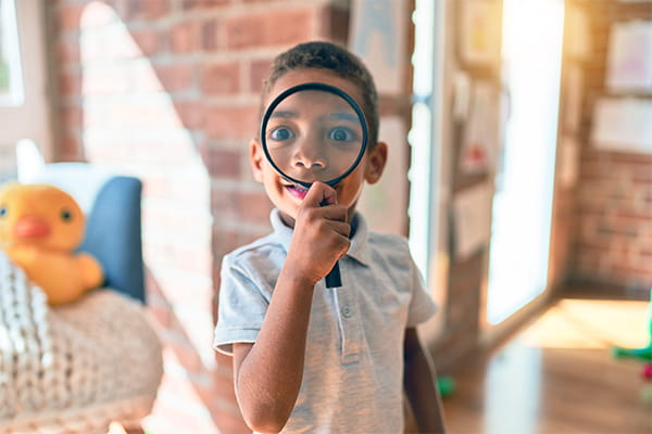 young boys with magnifying glass
