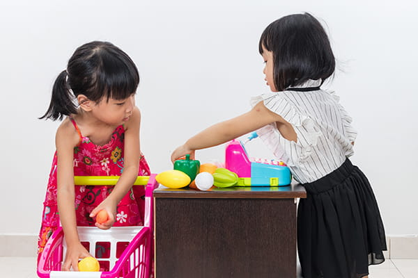 Two girls playing pretend shop