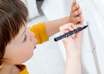 Child drawing on wall with felt tip marker
