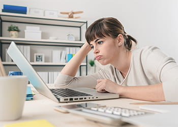 Bored woman looking at computer