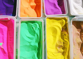 Containers of brightly coloured sand