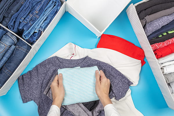 Woman folding clothes and packing into boxes
