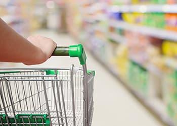 Woman pushing trolley around a supermarket