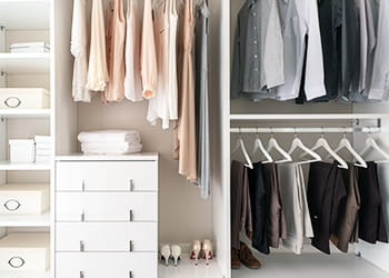 Clothes hanging neatly in a wardrobe