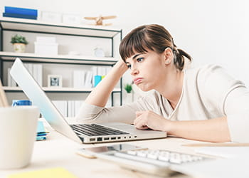 Lady looking bored staring at her computer