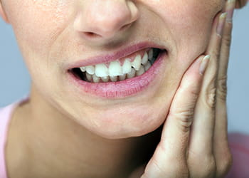Lady holding her face from toothache