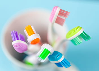 Colourful toothbrushes in a container