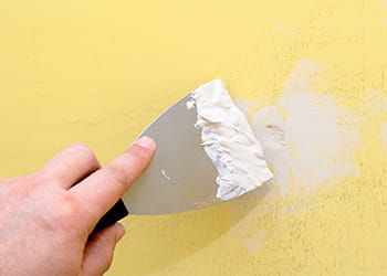 Hand filling in a hole in a wall with plaster