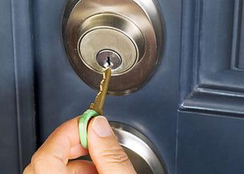 Door key going into a lock on a blue door