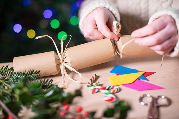 Hands tying homemade Christmas cracker