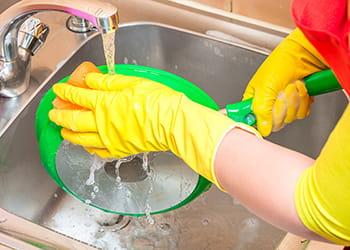 Person scrubbing saucepan under running tap