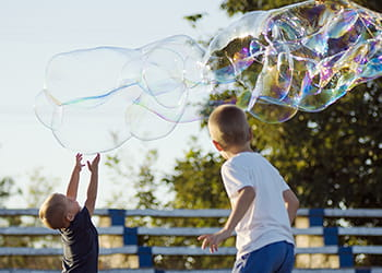 Kids making and playing with giant bubbles