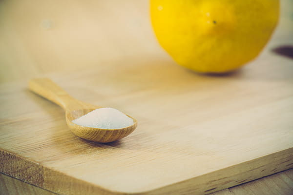 Lemon and a teaspoon of salt on a wooden chopping board
